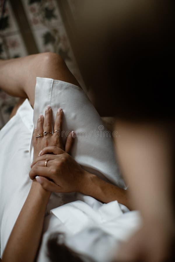 Kvinnliga händer som lägger på hennes korsade bencloseup Hon är att bära vita pyjamas royaltyfria bilder