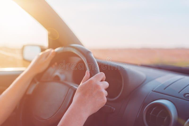 Kvinnliga händer som rymmer bilstyrninghjulet royaltyfria bilder