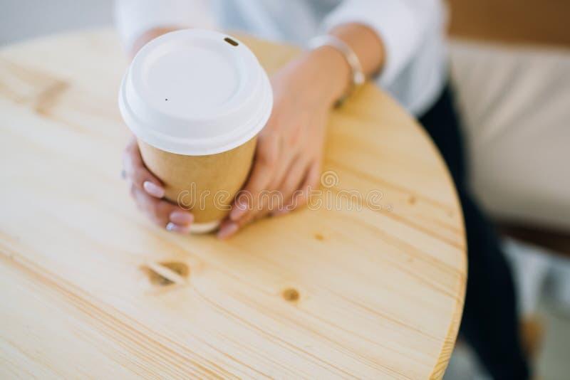 Kvinnliga händer som rymmer den återanvändbara kaffekoppen royaltyfri fotografi
