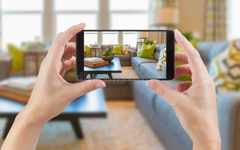 Kvinnliga händer som rymmer den smarta telefonen som visar fotoet av huset inter- royaltyfri fotografi