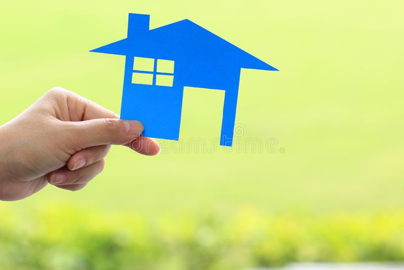 Kvinnliga händer som rymmer det blåa tomma pappers- huset på naturligt grönt bakgrunds-, fastighet- och äganderättegenskapsbegrep royaltyfri foto