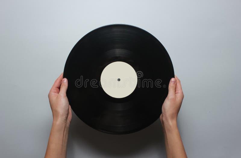 Kvinnliga händer som rymmer ett retro vinylrekord royaltyfria bilder
