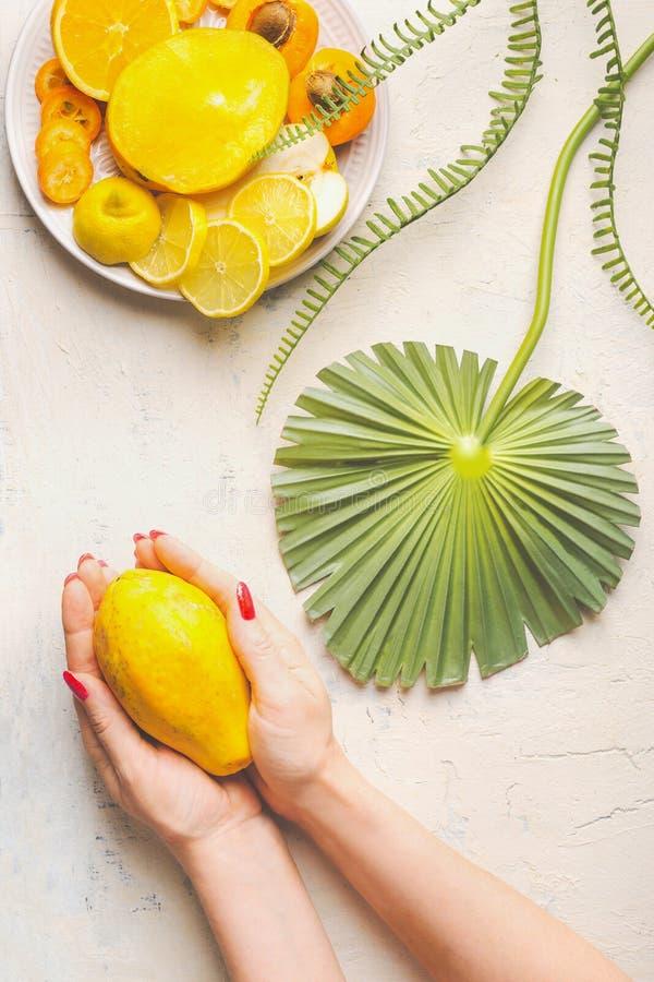 Kvinnliga händer som rymmer hel papayafrukt på den vita tabellen med tropiska sidor och plattan med gula skivade frukter, bästa s royaltyfri foto