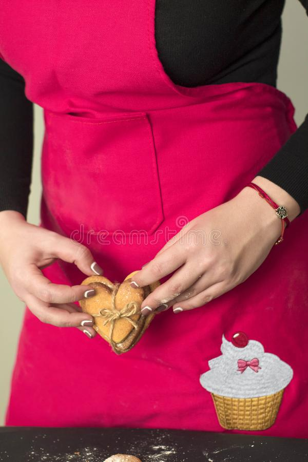 Kvinnliga händer som rymmer hjärtapepparkakan royaltyfri foto
