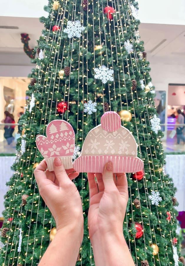 Kvinnliga händer som rymmer ljust rödbrun kakor i form av en hatt och tumvanten, mot bakgrunden av julgranen royaltyfria foton