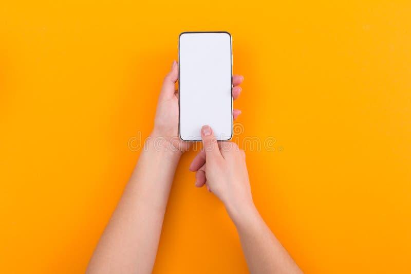 Kvinnliga händer som rymmer telefonen med den tomma skärmen på orange bakgrund arkivfoto