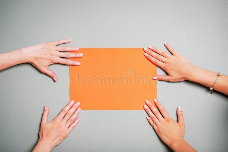 Kvinnliga händer som rymmer tomt orange papper eller pappersarket Gr? f?rgbakgrund kopiera avst?nd arkivbilder