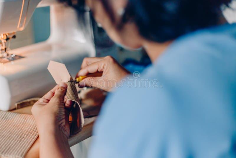 Kvinnliga händer som syr tyg med visaren på sömmerskaarbetsplatsen av att sy process händer som syr tyg på maskinen royaltyfri fotografi