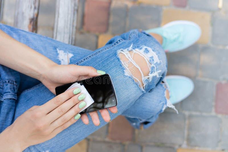 Kvinnliga händer torkar de antibacterial wipesna för pekskärmtelefonen arkivbilder