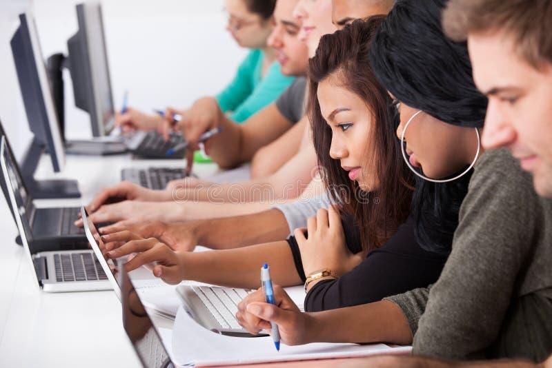 Kvinnliga högskolestudenter som använder bärbara datorn på skrivbordet royaltyfri bild