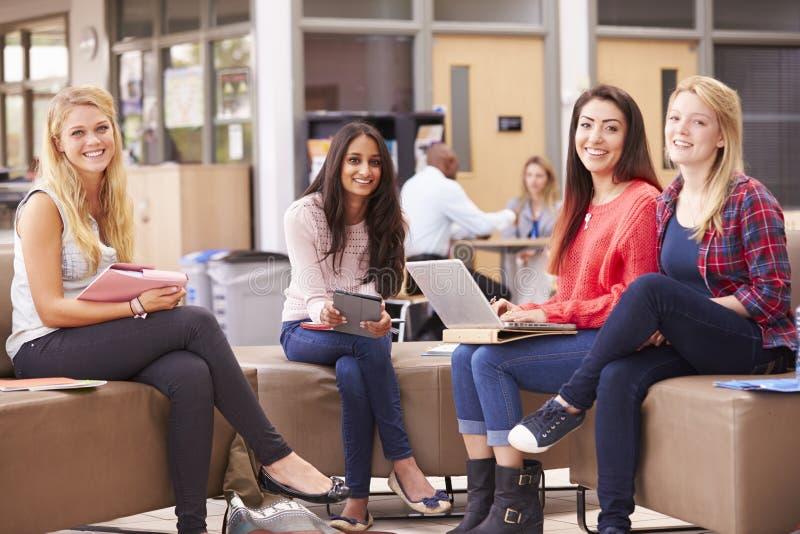 Kvinnliga högskolestudenter som tillsammans sitter och talar royaltyfria foton