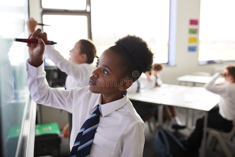 Kvinnliga högstadiumstudenter som bär enhetliga användande växelverkande Whiteboard under kurs royaltyfria bilder