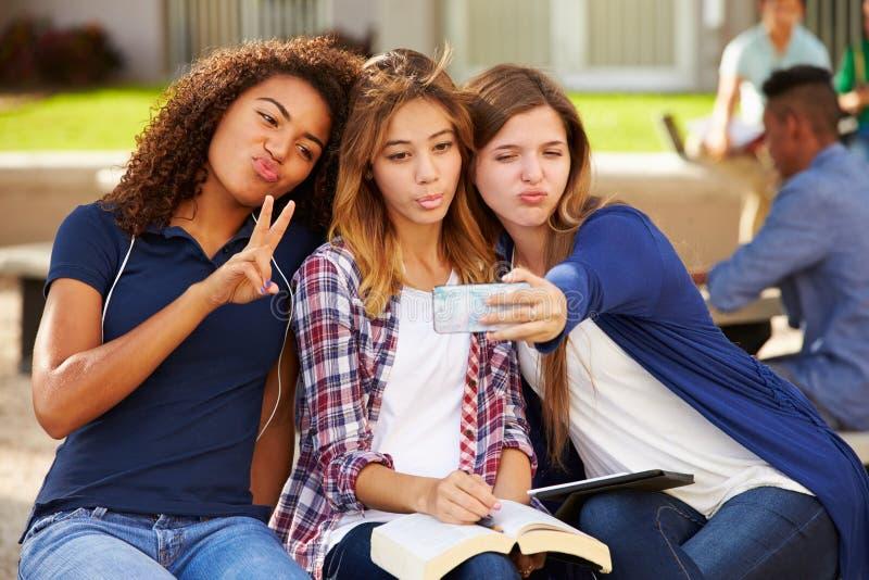 Kvinnliga högstadiumstudenter som tar Selfie på universitetsområde royaltyfri foto