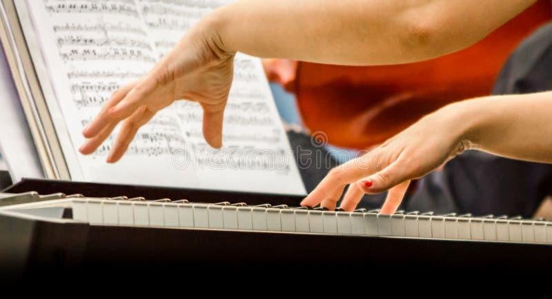 Kvinnliga h?nder av en pianistmusiker och pianotangenter st?nger sig upp arkivbild