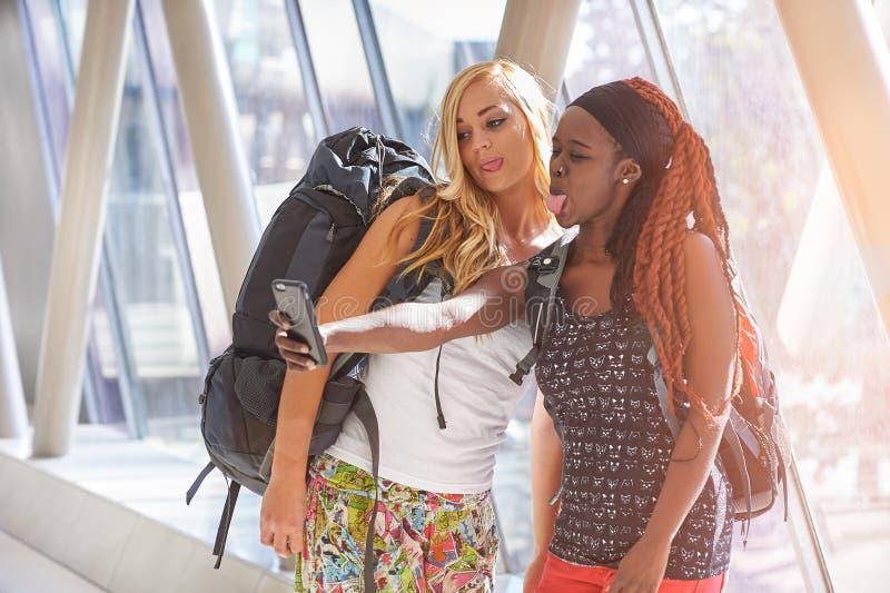 2 kvinnliga handelsresande i flygplatshallet som tar selfies royaltyfri bild