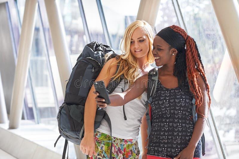 2 kvinnliga handelsresande i flygplatshallet som tar selfies arkivfoton