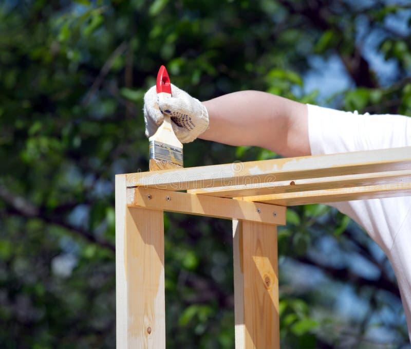 Kvinnliga handmålarfärger bryner en träcloseup för möblemang utomhus arkivbild