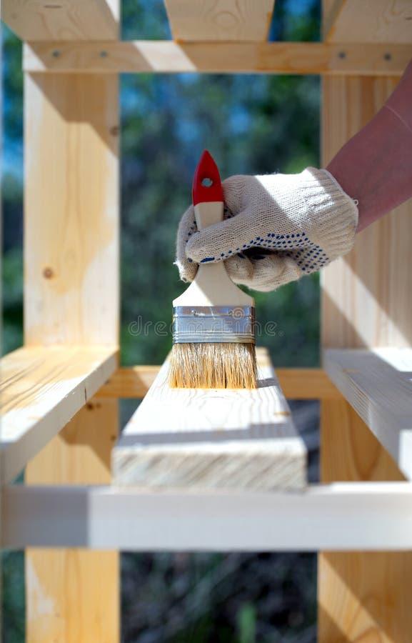 Kvinnliga handmålarfärger bryner ett trä bordlägga utomhus closeupen arkivfoton
