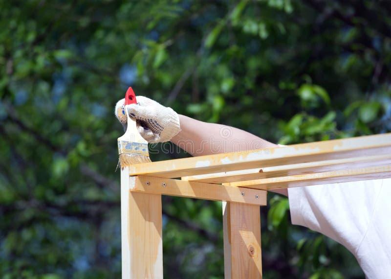 Kvinnliga handmålarfärger bryner ett trä bordlägga utomhus closeupen royaltyfri foto
