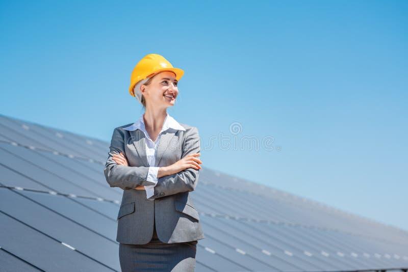 Kvinnliga investerare i ren energi framför solpaneler royaltyfri bild
