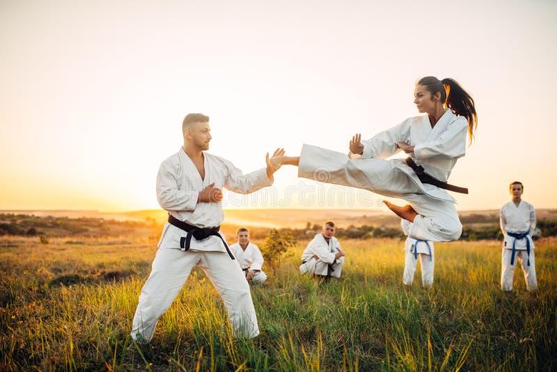 Kvinnliga karatekämpedrev sparkar i flykten royaltyfria bilder