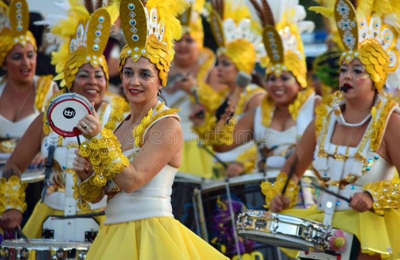 Kvinnliga karnevaldansare och handelsresande i flamboyanta gula dräkter royaltyfri fotografi
