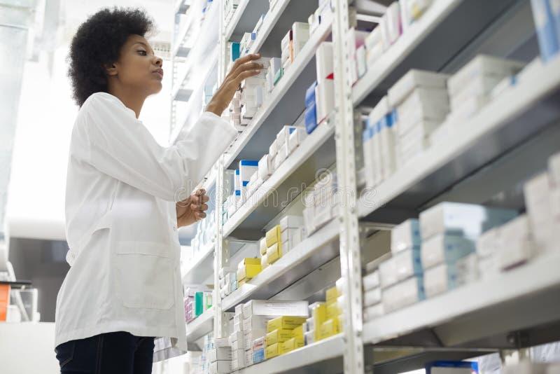 Kvinnliga kemistArranging Stock In hyllor på apotek royaltyfria bilder