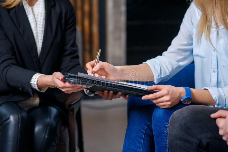Kvinnliga klienter som undertecknar avtalet f?r att k?pa det nya huset, framl?nges royaltyfri bild