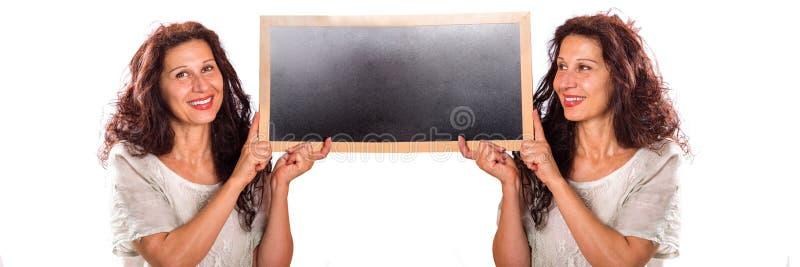 Kvinnliga klon som rymmer den svart tavlan royaltyfri bild