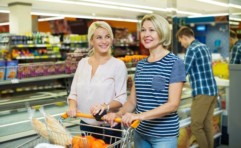 Kvinnliga kunder nära visar med djupfryst mat royaltyfria foton