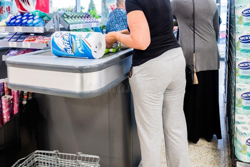 Kvinnliga kunder på supermarket checkout att betala för deras gods arkivfoton