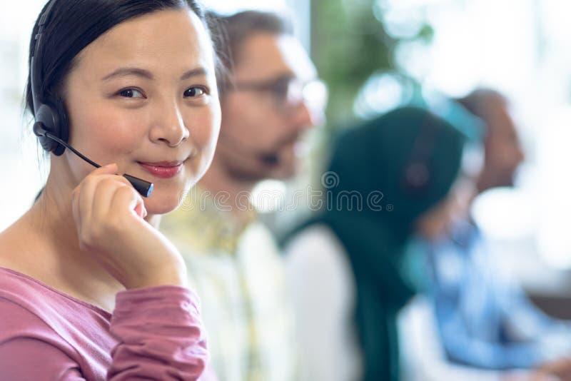 Kvinnliga kundtjänstledare som talar på hörlurar med mikrofon på skrivbordet royaltyfri foto