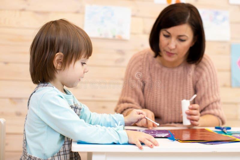 Kvinnliga lärare leker med förskolebarn på dagvårdscenter arkivfoto