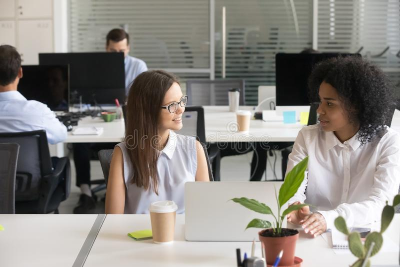 Kvinnliga mångfaldkollegor diskuterar datorarbete arkivfoton