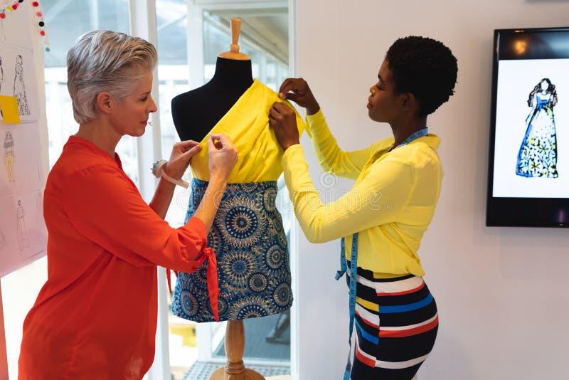 Kvinnliga modeformgivare som använder mäta bandet på en skyltdocka royaltyfri bild