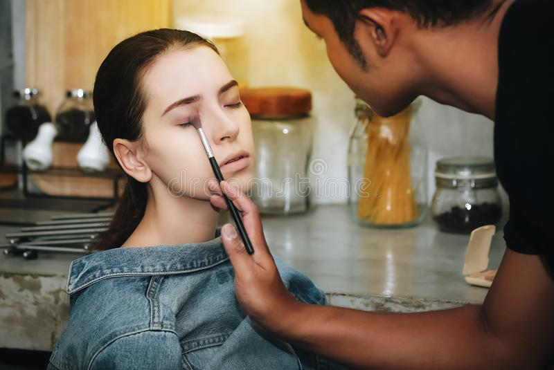 Kvinnliga modeller färgar deras framsidor med yrkesmässig makeup royaltyfri foto