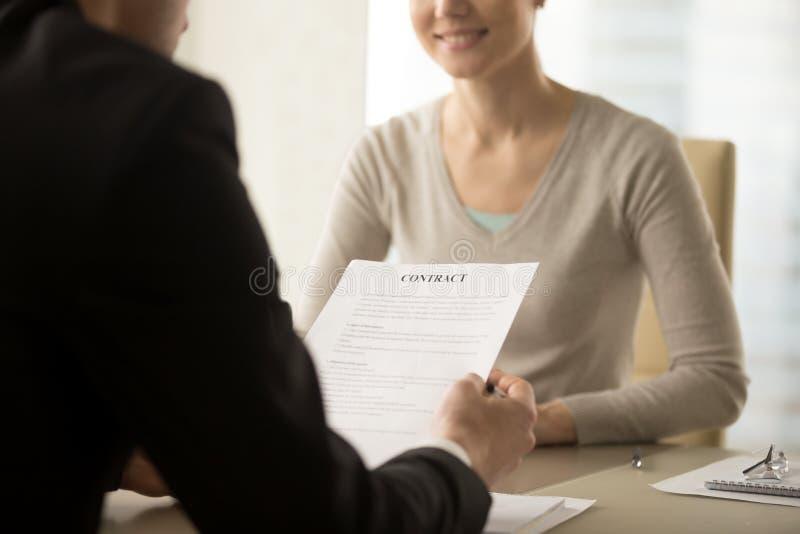 Kvinnliga och manliga företagsledare som studerar avtalet arkivbild