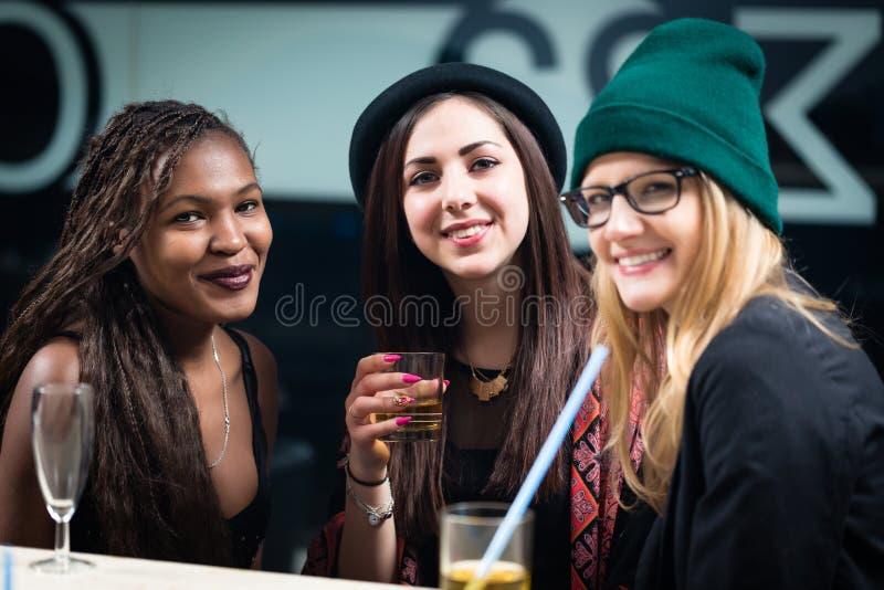 Kvinnliga olika vänner som tycker om drinkar på partiet arkivfoton