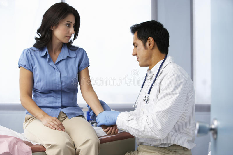 Kvinnliga patients för doktor In Surgery Taking puls arkivfoton