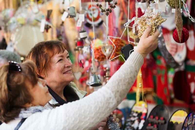 Kvinnliga pensionärer som köper garneringar X-mas royaltyfri bild