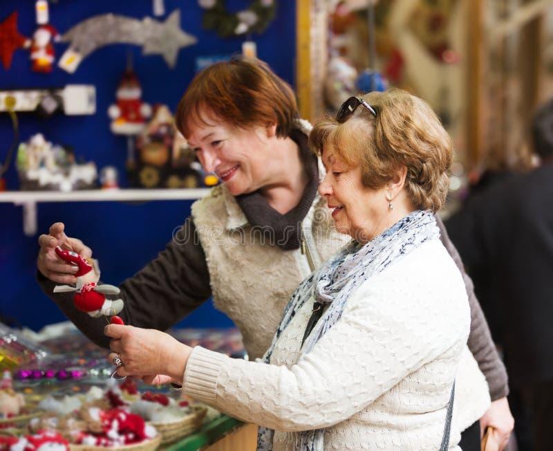 Kvinnliga pensionärer som köper garneringar X-mas fotografering för bildbyråer