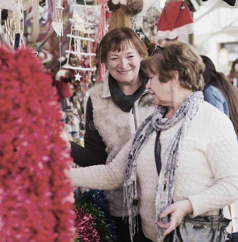 Kvinnliga pensionärer som köper garneringar X-mas arkivbilder