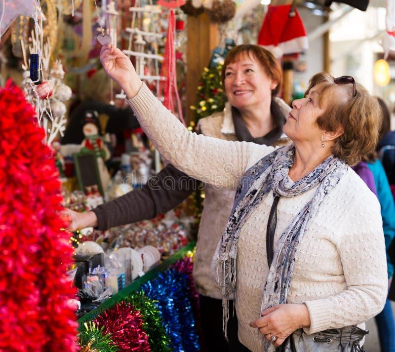 Kvinnliga pensionärer som köper garneringar X-mas royaltyfria foton
