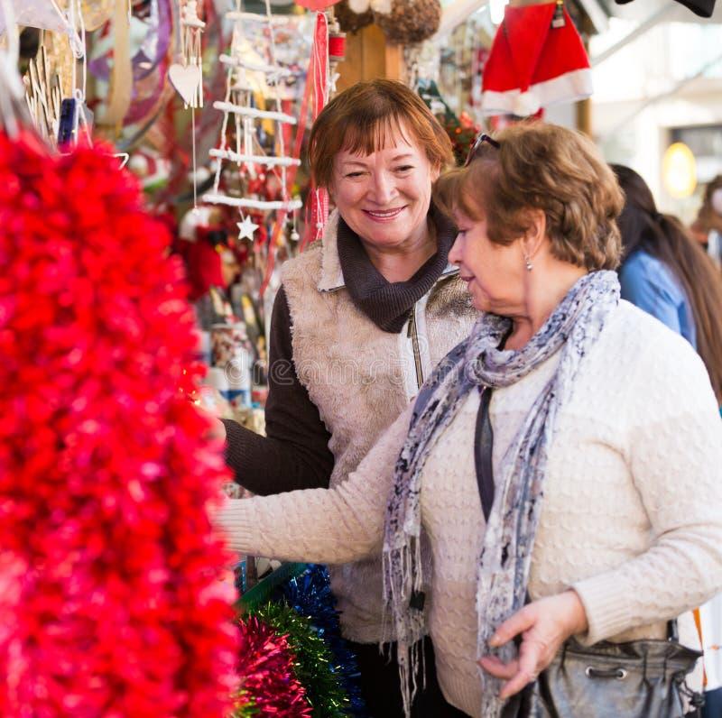 Kvinnliga pensionärer som köper garneringar X-mas arkivfoton