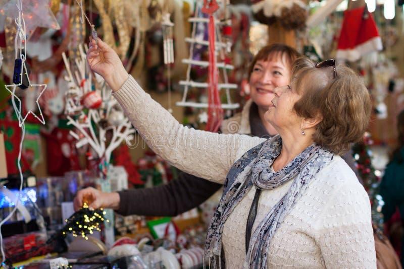 Kvinnliga pensionärer som köper garneringar X-mas på mässan arkivfoto
