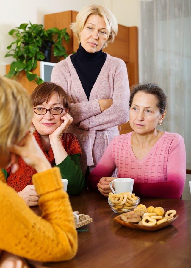 Kvinnliga pensionärer som lyssnar till den ledsna berättelsen av deras vän royaltyfria foton