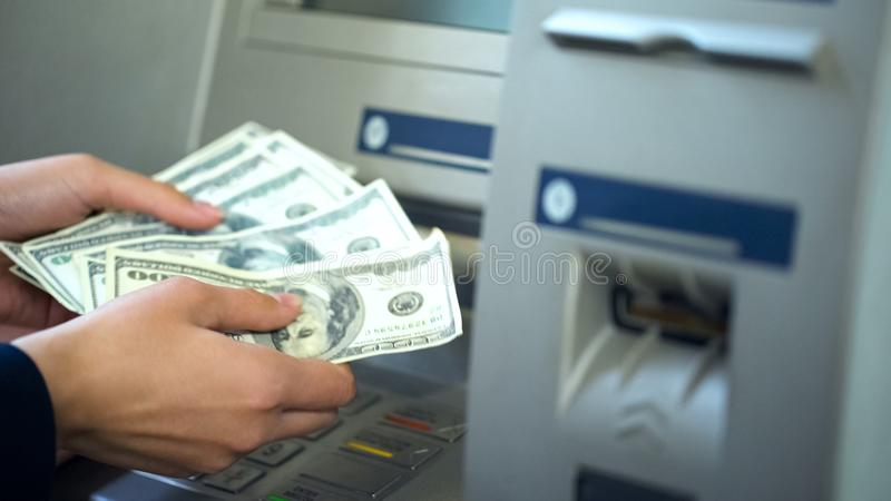 Kvinnliga räknande dollar som återtas från ATM, 24h service, lätt packa ihop operation arkivbild