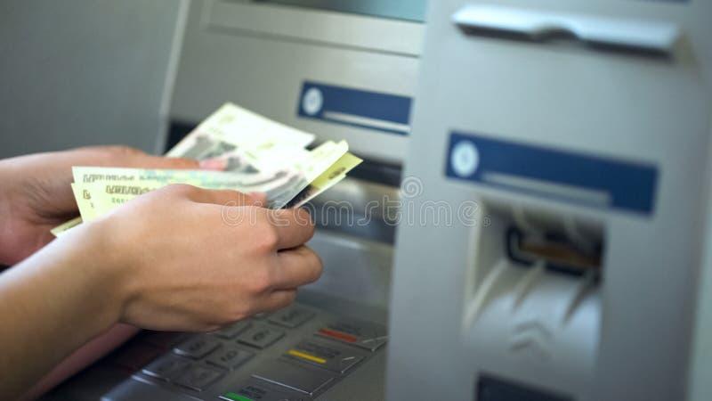 Kvinnliga räknande ryska rubel som återtas från ATM, 24h service, lätta bankrörelsen royaltyfri fotografi