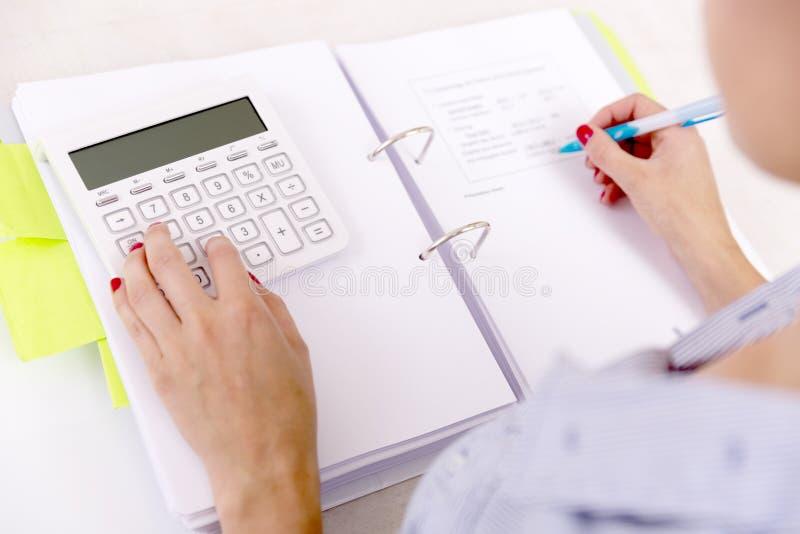 Kvinnliga revisor- eller bankirdanandeberäkningar Besparingar finansbegrepp arkivfoton