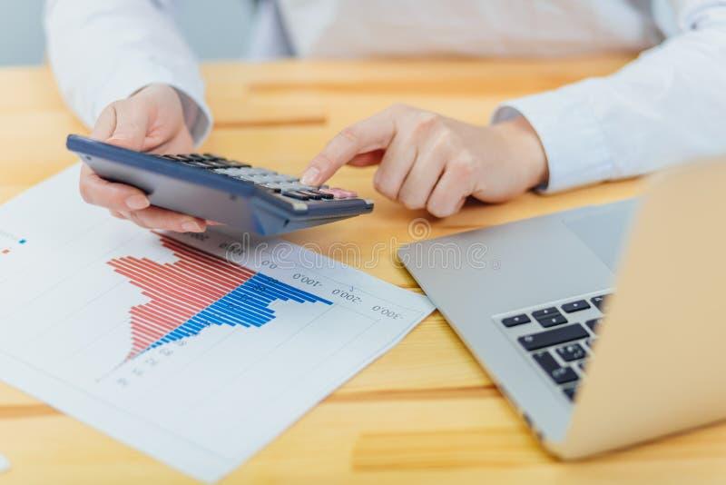 Kvinnliga revisorer använder en räknemaskin sammanfattningsvis beloppet av inkomst, kostnader och årlig statistik för att resumer royaltyfria bilder